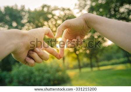 Closeup of hands showing heart shape with nature sunset background.