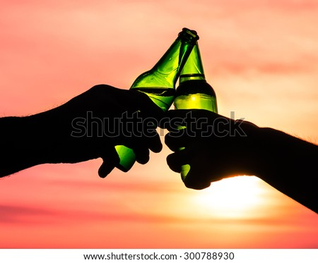 Closeup of hands toasting with bottles of beer - stock photo