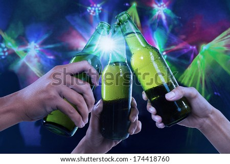 Closeup of hands toasting with bottles of beer at the party club - stock photo