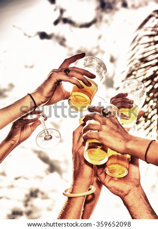 Closeup of hands toasting with glasses of beer. - stock photo