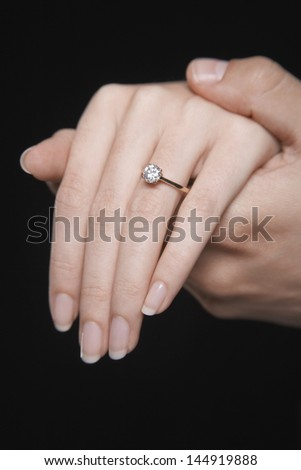 Closeup of hands together showing woman's engagement ring against black background
