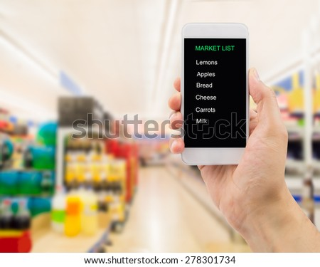 Closeup of hands using smart phone in the supermarket