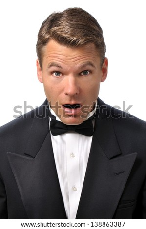 Closeup of handsome Caucasian man in tuxedo with look of surprise on face with white background
