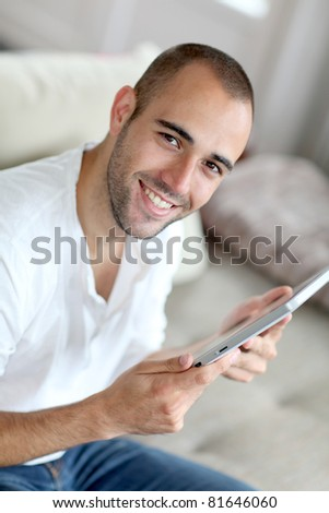 Closeup of handsome man web surfing on touchpad - stock photo