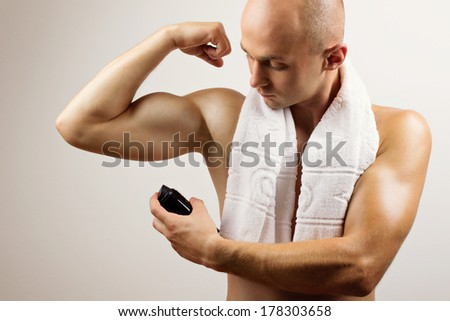 Closeup of handsome young Caucasian shirtless man with towel applying antiperspirant deodorant after shower. Man refreshing after workout. Body care and hygiene concept. - stock photo