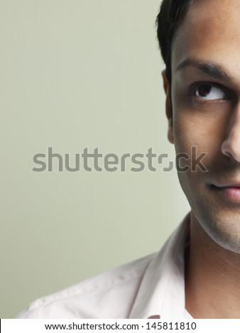 Closeup of handsome young man looking up on colored background - stock photo