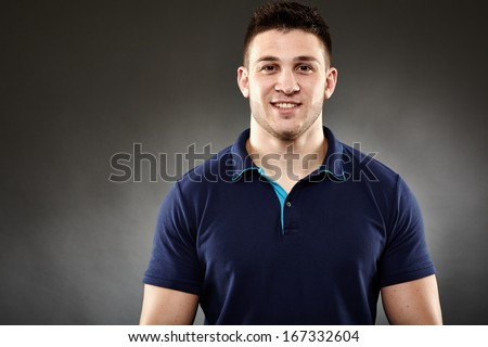 Closeup of handsome young man wearing a navy blue polo t-shirt - stock photo