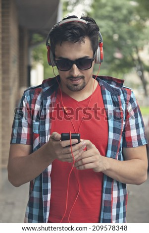 Closeup Of Handsome Young Man With Headphones Listening To Music Outdoors - stock photo