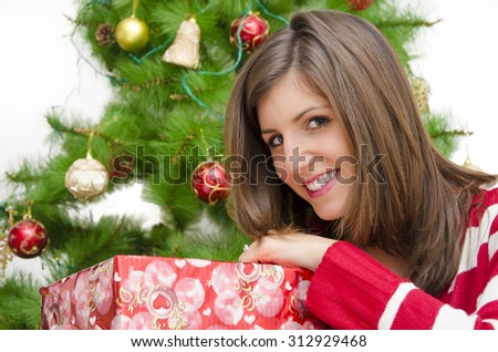 Closeup of happy beautiful brunette in front of Christmas tree with a gift