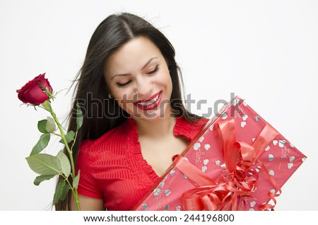 Closeup of happy beautiful woman smiling, holding wrapped gift and a rose - stock photo
