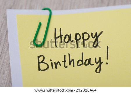 Closeup of Happy Birthday ! written on yellow paper note with paperclip - stock photo