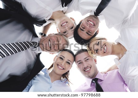 Closeup of happy business people with their heads together representing concept of ftiendship and teamwork isolated on white background - stock photo
