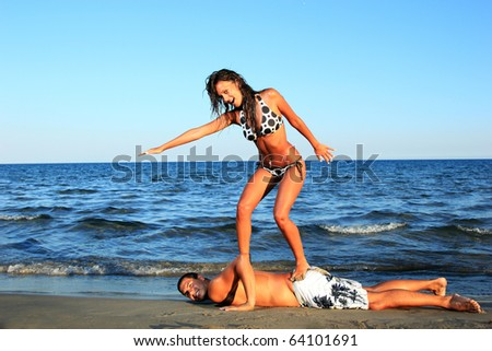 Closeup of happy couple at the beach gril surfing on her boyfriend's back - stock photo