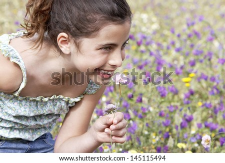 Closeup of happy cute little girl smelling flower at field - stock photo