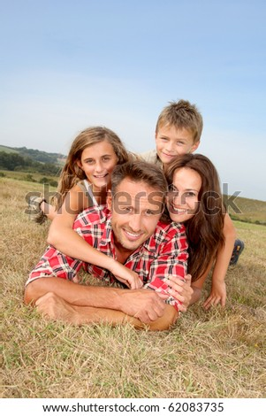 Closeup of happy family lying in grass - stock photo