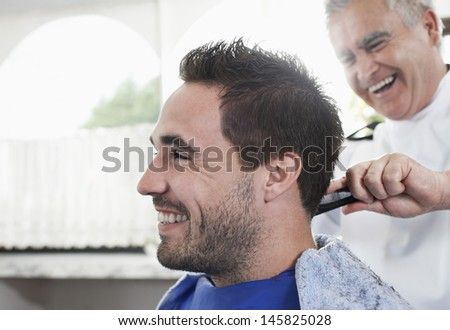 Closeup of happy man getting an haircut from barber in hair salon - stock photo