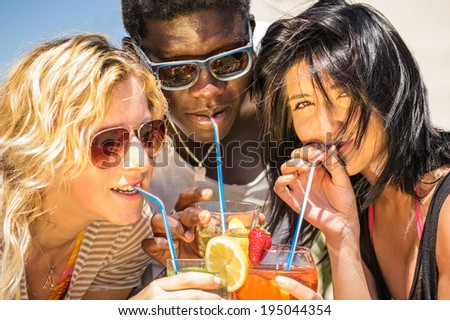 Closeup of happy multiethnic friends drinking cocktails - stock photo
