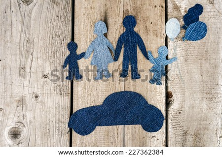 Closeup of happy paper family on vintage wooden background. Family made from jeans fabric - stock photo