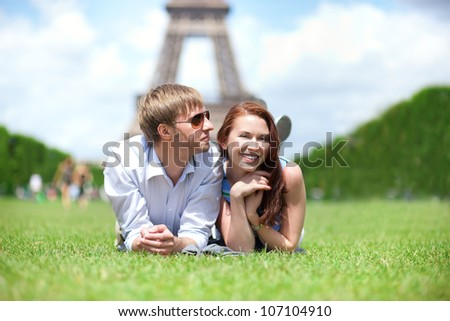 Closeup of happy positive couple laying on the grass in Paris - stock photo