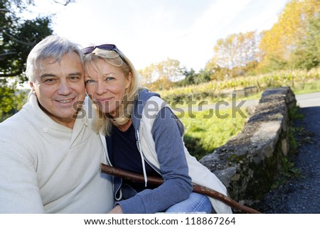 Closeup of happy senior couple sitting by river - stock photo