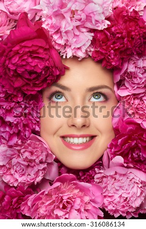 Closeup of happy smiling beauty woman face with perfect skin and professional makeup in peony flowers looking up - stock photo