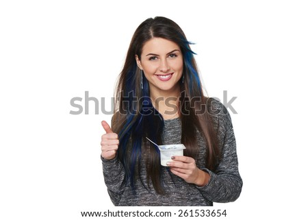 Closeup of happy smiling healthy woman holding yoghurt and gesturing thumb up, isolated on white - stock photo
