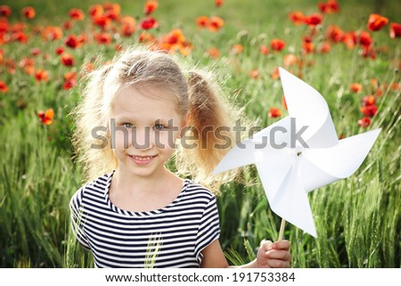 Closeup of happy smiling little girl standing on the poppy meadow and holding toy white pinwheel windmill - stock photo
