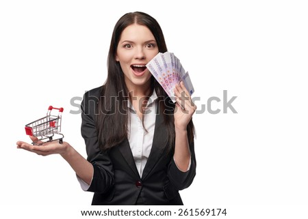 Closeup of happy surprised woman with euro cash money in one hand and small empty shopping cart in other hand, isolated on white background