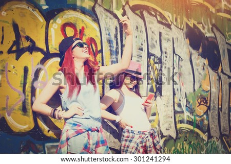 Closeup of happy two teenage girls in urban modern casual summer outfits with hats and sunglasses taking a selfie and texting on smartphones against colorful wall. - stock photo