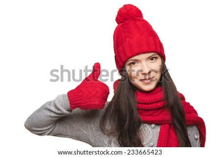 Closeup of happy woman wearing red warm winter hat, scarf and gloves gesturing thumb up, over white background