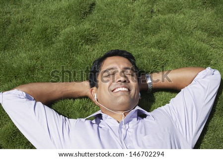 Closeup of happy young businessman listening music while lying on grass - stock photo