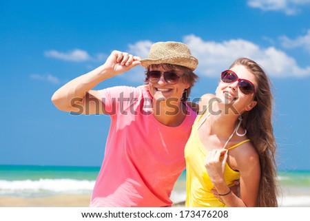 Closeup of happy young couple on beach smiling - stock photo