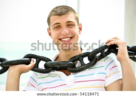 Closeup of happy young guy with enormous chain