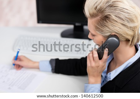 Closeup of happy young woman using phone while writing on paper in office - stock photo