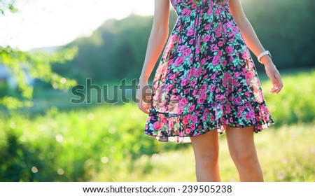 Closeup of happy young woman wearing light summer dress with flowers on sunny day outdoors - stock photo
