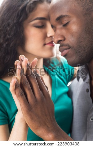 Closeup of happy young woman with boyfriend spending time together. Closeup portrait of african young couple isolated on white background. - stock photo