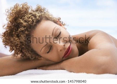 Closeup of happy young woman with eyes closed lying on massage table outdoors - stock photo