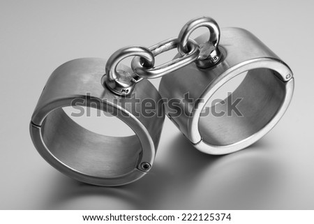 closeup of hard steel handcuffs or cuffs - stock photo