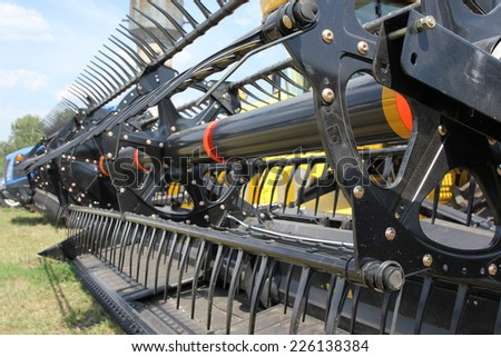 Closeup of harvesting machinery while working the field. - stock photo