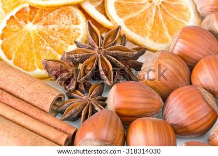 Closeup of hazelnuts, cinnamon sticks, anise and orange slices - stock photo