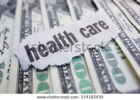 Closeup of health care newspaper headline, on cash                                - stock photo