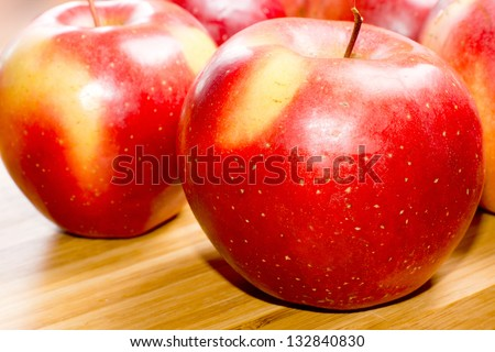 Closeup of healthy ripe red apples sprinkled with fine water droplets on a wooden table top - stock photo