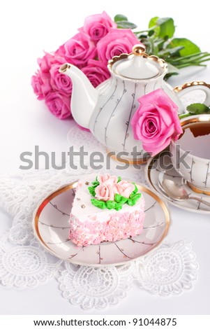 Closeup of heart-shaped cake with roses and cup of tea