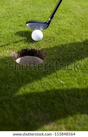 Closeup of hole on golf field - stock photo