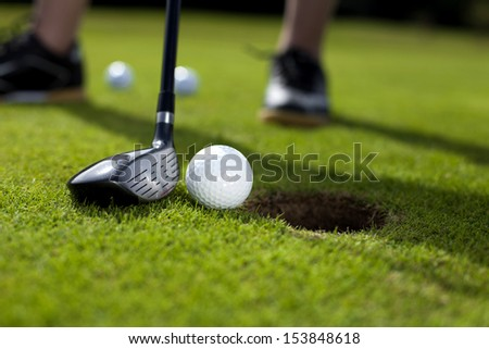 Closeup of hole on golf field - stock photo
