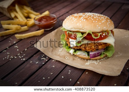 Closeup of home made burgers on sesame buns with beef patties and fresh salad ingredients on wooden background - stock photo