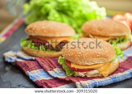 Closeup of home made burgers on wooden table - stock photo