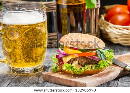 Closeup of homemade burger and a cold beer - stock photo