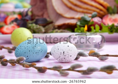 Closeup of honey ham on Easter table with eggs, flowers and decoration - stock photo