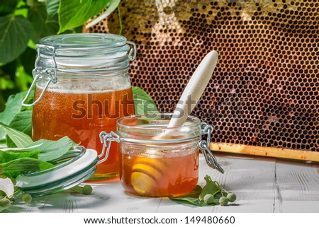 Closeup of honey in a jar and honeycomb - stock photo